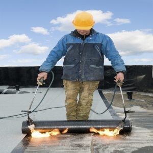 Man fixing flat roof in scotland